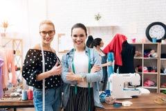 Tre ragazze alla fabbrica dell'indumento Stanno dando i pollici su hanno finito il nuovo vestito immagini stock libere da diritti