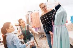 Tre ragazze alla fabbrica dell'indumento Stanno discutendo la progettazione di nuovo vestito immagini stock