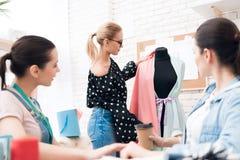 Tre ragazze alla fabbrica dell'indumento Stanno discutendo la progettazione di nuovo vestito immagine stock libera da diritti