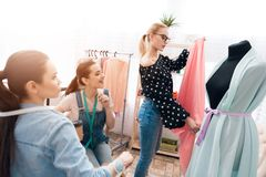 Tre ragazze alla fabbrica dell'indumento Stanno discutendo la progettazione di nuovo vestito immagine stock