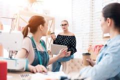 Tre ragazze alla fabbrica dell'indumento Stanno discutendo la progettazione per il nuovo vestito fotografie stock libere da diritti