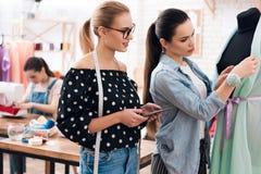 Tre ragazze alla fabbrica dell'indumento Stanno esaminando desing di nuovo vestito fotografia stock libera da diritti