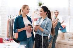 Tre ragazze alla fabbrica dell'indumento Stanno esaminando i modelli ed il caffè bevente immagini stock libere da diritti