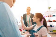 Tre ragazze alla fabbrica dell'indumento Stanno scegliendo i bottoni per il nuovo vestito immagine stock libera da diritti
