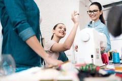 Tre ragazze alla fabbrica dell'indumento Stanno scegliendo i bottoni per il nuovo vestito fotografia stock libera da diritti