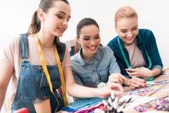 Tre ragazze alla fabbrica dell'indumento Stanno scegliendo i perni per il nuovo vestito fotografie stock libere da diritti