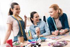 Tre ragazze alla fabbrica dell'indumento Stanno scegliendo i perni per il nuovo vestito fotografie stock