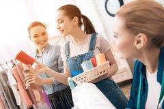 Tre ragazze alla fabbrica dell'indumento Stanno scegliendo il colore del filo per il nuovo vestito fotografie stock