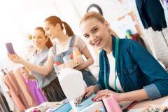 Tre ragazze alla fabbrica dell'indumento Stanno scegliendo il colore del filo per il nuovo vestito immagine stock