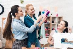 Tre ragazze alla fabbrica dell'indumento Stanno scegliendo il tessuto per il nuovo vestito fotografia stock