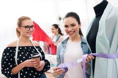 Tre ragazze alla fabbrica dell'indumento Stanno scegliendo la vita per il nuovo vestito fotografia stock