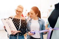 Tre ragazze alla fabbrica dell'indumento Stanno scegliendo la vita per il nuovo vestito fotografia stock libera da diritti