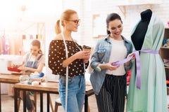 Tre ragazze alla fabbrica dell'indumento Stanno scegliendo la vita per il nuovo vestito immagini stock libere da diritti