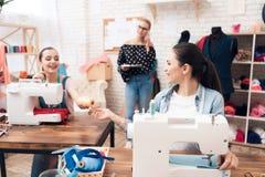 Tre ragazze alla fabbrica dell'indumento Stanno sedendo dietro le macchine per cucire immagine stock libera da diritti
