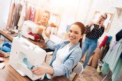 Tre ragazze alla fabbrica dell'indumento Stanno sedendo dietro le macchine per cucire fotografia stock