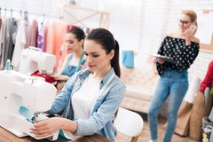 Tre ragazze alla fabbrica dell'indumento Stanno sedendo dietro le macchine per cucire fotografie stock