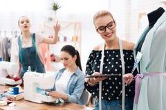 Tre ragazze alla fabbrica dell'indumento Stanno sedendo dietro le macchine per cucire e stanno esaminando la progettazione di nuo immagine stock