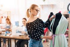 Tre ragazze alla fabbrica dell'indumento Stanno sedendo dietro le macchine per cucire e stanno prendendo le misure di nuovo vesti fotografia stock