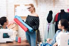 Tre ragazze alla fabbrica dell'indumento Stanno sedendo dietro le macchine per cucire e stanno scegliendo il tessuto per il nuovo fotografia stock