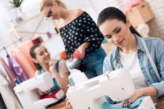 Tre ragazze alla fabbrica dell'indumento Stanno sedendo dietro le macchine per cucire e scegliere infila per il nuovo vestito immagini stock