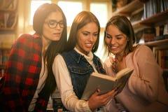 Tre ragazze allegre degli studenti in biblioteca che leggono insieme libro Fotografie Stock