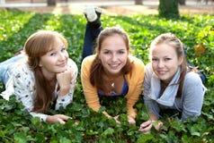 Tre ragazze allegre dell'allievo che pongono sull'erba Immagine Stock