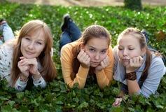 Tre ragazze allegre dell'allievo che pongono sull'erba Fotografia Stock Libera da Diritti