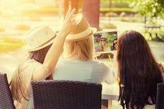 Tre ragazze attraenti dei pantaloni a vita bassa che prendono un selfie con la compressa digitale fotografie stock