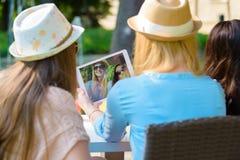 Tre ragazze attraenti dei pantaloni a vita bassa che prendono un selfie con la compressa digitale fotografia stock
