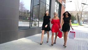 Tre ragazze che camminano con i sacchetti della spesa, tre belle giovani donne degli amici con i sacchetti della spesa stock footage