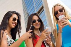 Tre ragazze che chiacchierano con i loro smartphones alla città universitaria Immagini Stock
