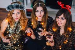 Tre ragazze che esaminano macchina fotografica un partito della casa Fotografia Stock
