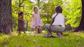 Tre ragazze che giocano nel parco sull'erba vicino all'albero archivi video