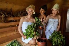 Tre ragazze che si rilassano nella sauna Fotografia Stock