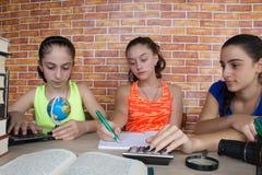 Tre ragazze che si siedono allo scrittorio a casa, facendo compito Un ritratto di studio grazioso dello studente della High Schoo Fotografia Stock Libera da Diritti