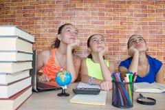 Tre ragazze che si siedono allo scrittorio a casa, facendo compito Un ritratto di studio grazioso dello studente della High Schoo Immagini Stock Libere da Diritti