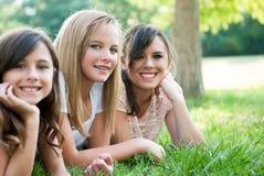 Tre ragazze che si siedono nell'erba Fotografia Stock