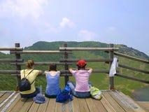 Tre ragazze che si siedono sulla piattaforma di osservazione che esamina le montagne immagine stock libera da diritti