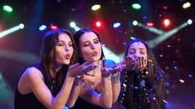Tre ragazze che soffiano i coriandoli variopinti al partito video d archivio