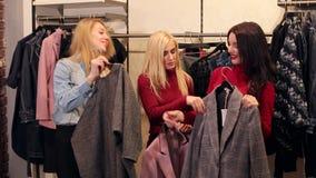Tre ragazze comprano i nuovi vestiti in un deposito di modo in un grande centro commerciale archivi video