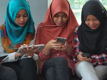 Tre ragazze con gli aggeggi di elettronica immagini stock libere da diritti