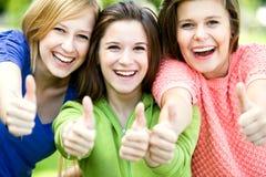 Tre ragazze con i pollici in su Immagine Stock
