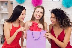 Tre ragazze con i sacchetti della spesa che prendono i ress rossi dalla borsa Stanno celebrando donne ` s il giorno l'8 marzo immagini stock