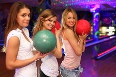 Tre ragazze con le sfere si levano in piedi nel randello di bowling Fotografie Stock Libere da Diritti