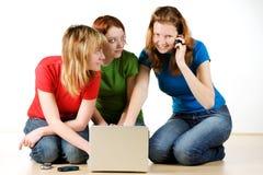 Tre ragazze con un computer portatile Immagine Stock