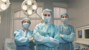 Tre ragazze curano nella sala operatoria decollano la maschera di protezione e sorridono Fotografia Stock Libera da Diritti