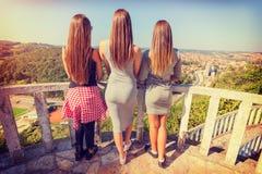 Tre ragazze da dietro panorama di sorveglianza della città Fotografia Stock