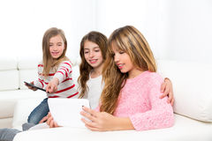 Tre ragazze degli amici della sorella del bambino che giocano insieme al pc della compressa Fotografie Stock Libere da Diritti
