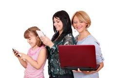 Tre ragazze delle generazioni con la compressa ed il computer portatile del telefono Fotografia Stock