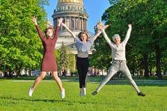 Tre ragazze dello studente saltano su sui precedenti del gatto del ` s della st Isaac Fotografie Stock Libere da Diritti